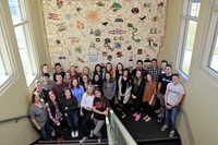 Graduating seniors from each high school stand in front of the mural they helped create while students at Fouse Elementary School.