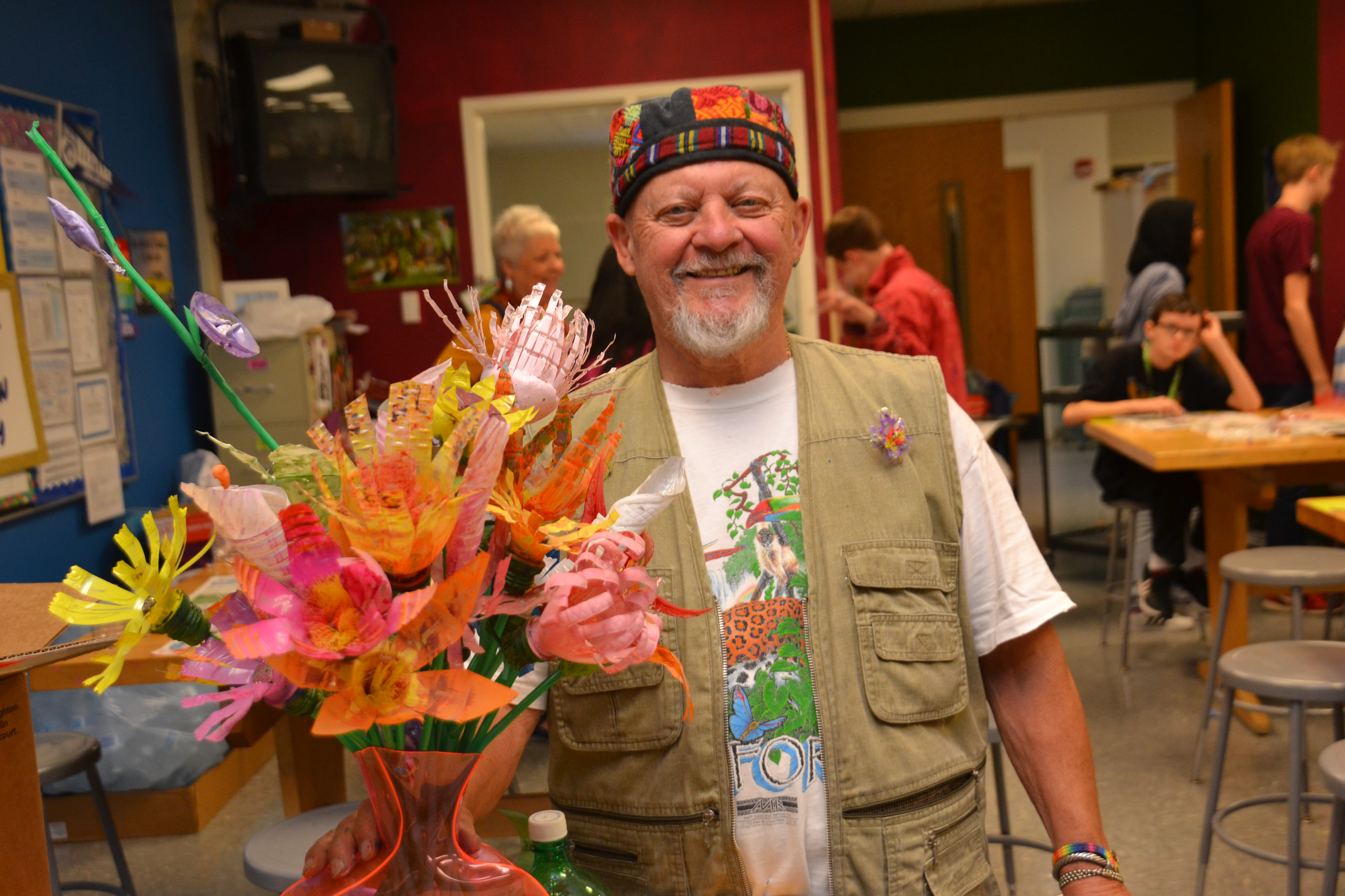 Artist Eric Marlow holding a beautiful floral arrangement using plastic water bottles and two-liter jugs.