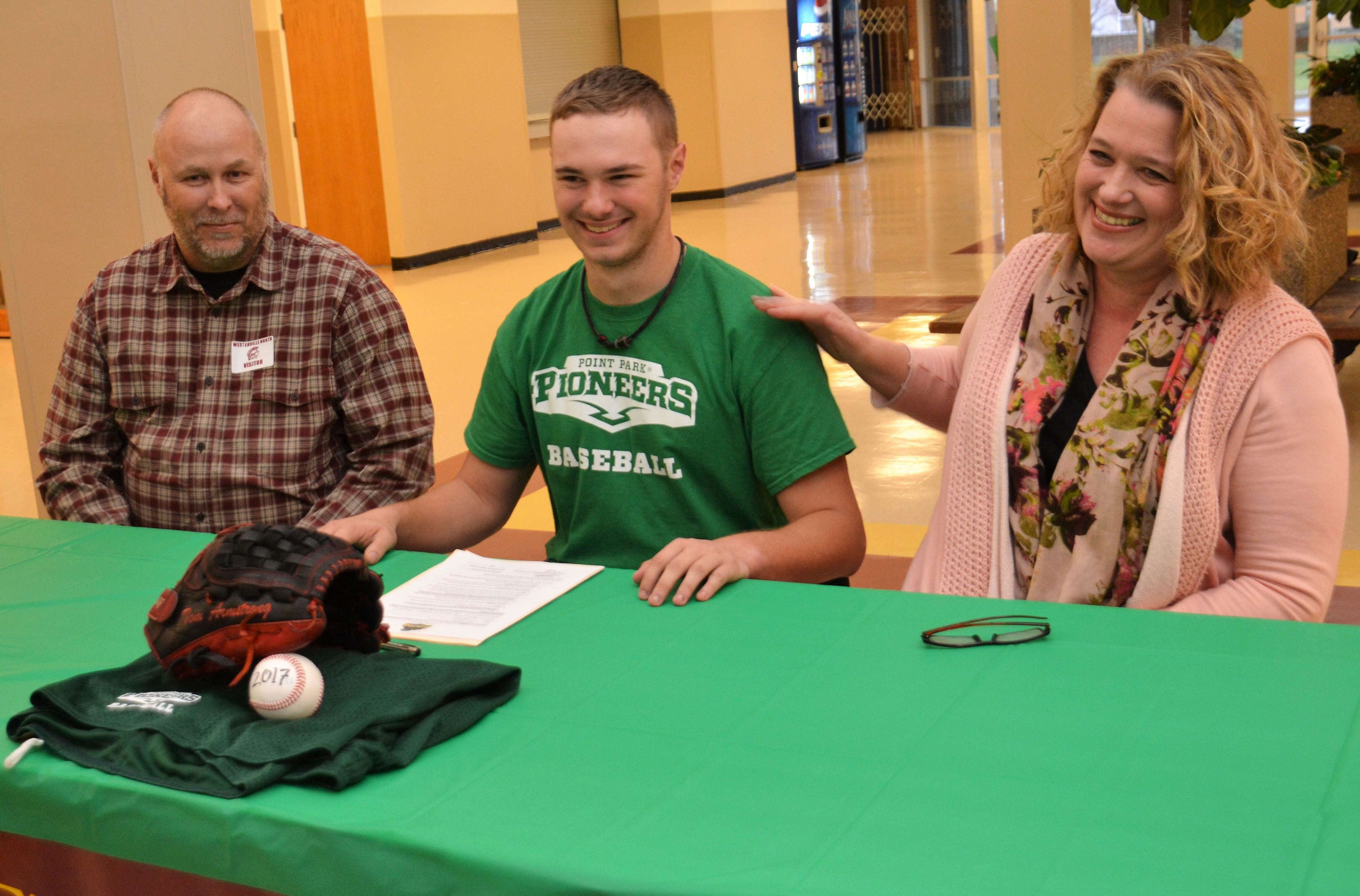 Tom Armstrong and his parents smile after he signs his Letter of Intent