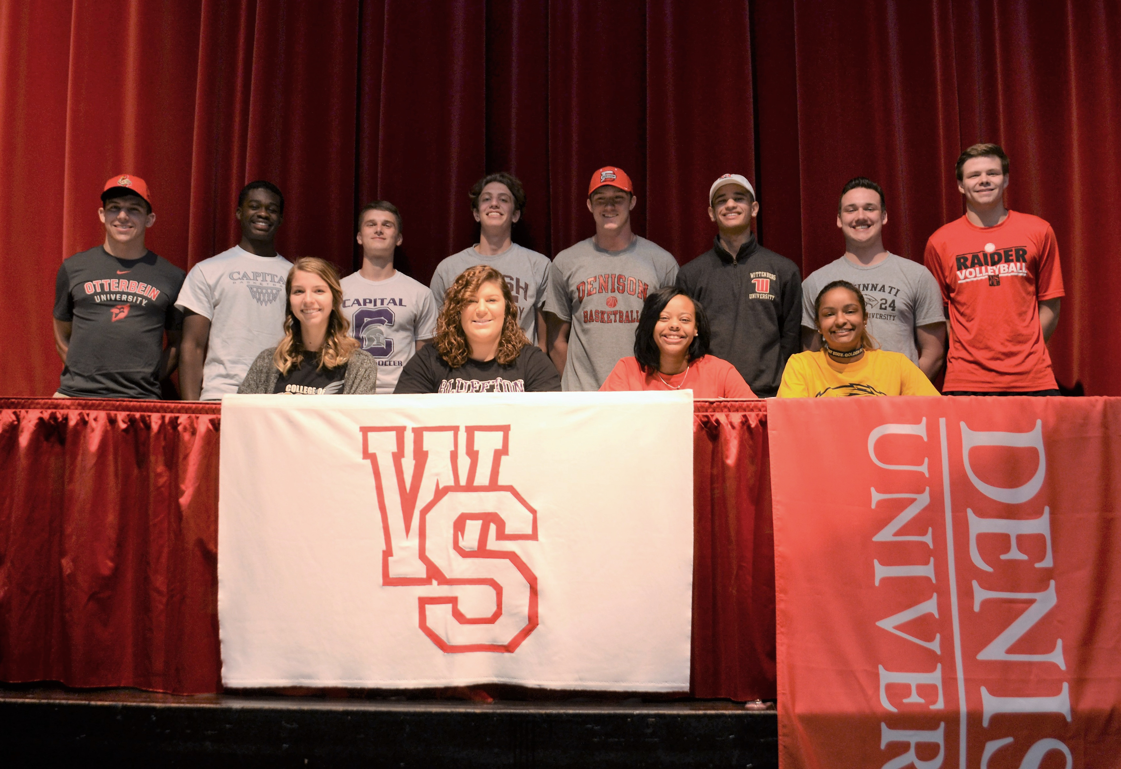Student athletes on stage after signing Letters of Intent
