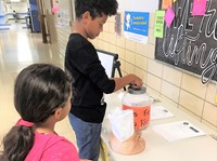 A fifth grader makes a donation.