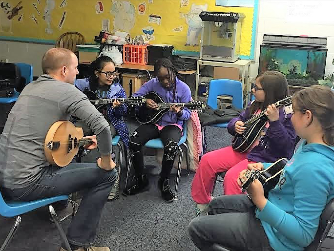Mick Broderick giving mandolin lessons to youngsters