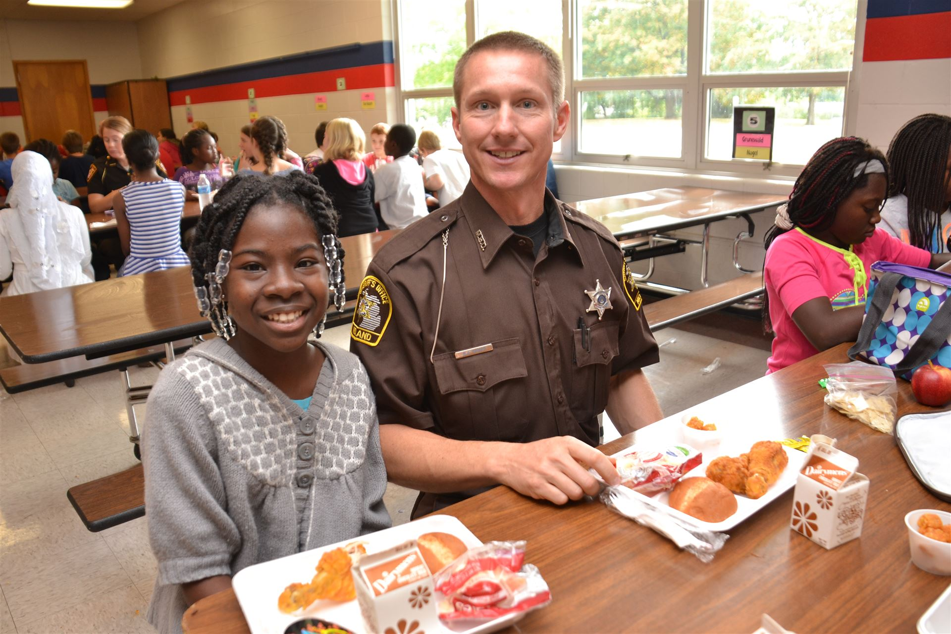 A student eating lunch with a DARE officer