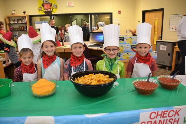 Alcott first grade students prepare meals in El Toro Loco restaurant.